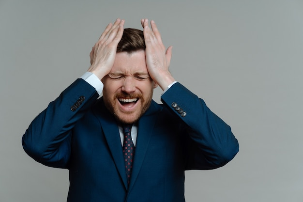 양복 느낌에 좌절 된 비즈니스 남자 스트레스와 재정 문제 걱정, 회색 배경에 서있는 동안 나쁜 소식을 얻는 동안 손으로 머리를 만지는 사람. 사업 실패 개념