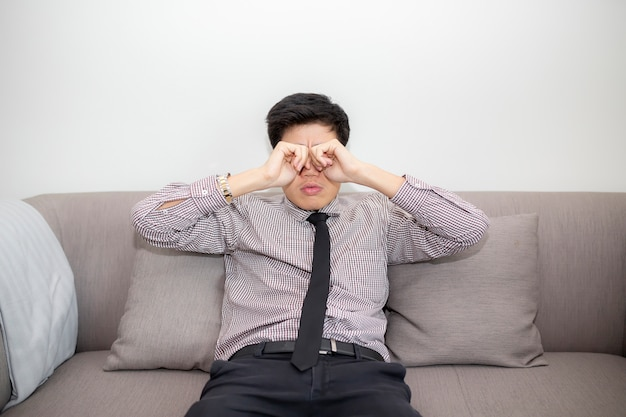 イライラしたビジネスマンは、長時間のコンピューター作業の後に視力が過度に緊張するため、目に痛みを感じます。ノートパソコンの前で目をマッサージ疲れた若い男。職場での目の疲労、頭痛、片頭痛。