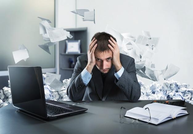 彼の頭を保持している欲求不満のビジネスマンは、オフィスに座っています