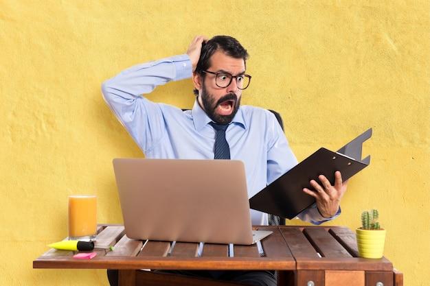Разочарованный бизнесмен в своем офисе со своей папкой