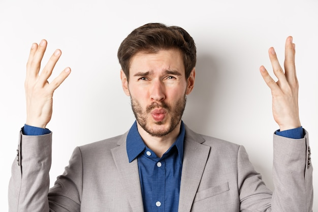 Frustrated businessman shaking hands and asking wtf what happened, looking disappointed and shocked at camera, scolding employee, white background.