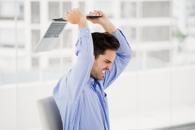 Frustrated businessman throwing laptop