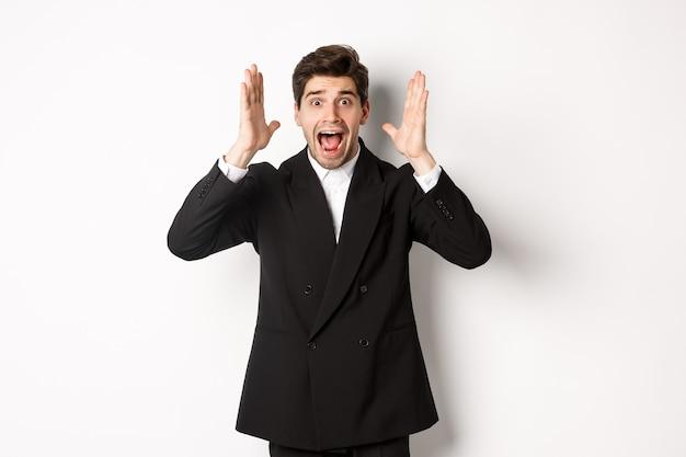 Uomo frustrato e preoccupato in abito nero, urlando in preda al panico e guardando qualcosa di scioccante, in piedi su sfondo bianco