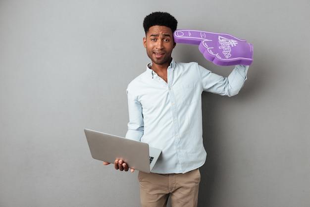 Разочарованный путать африканских человек, держащий портативный компьютер