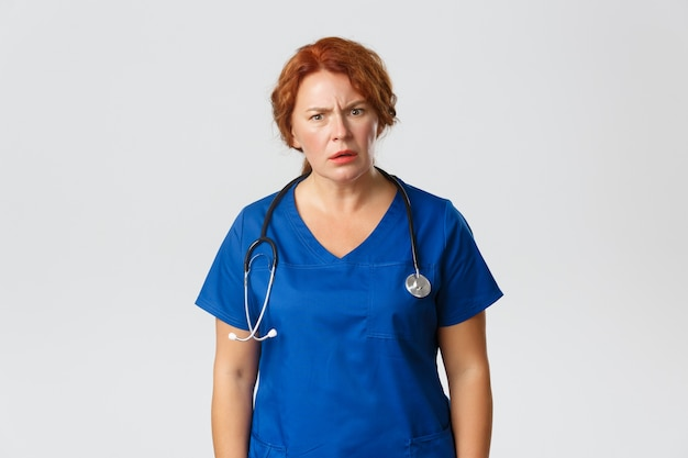 Frustrated and confused redhead middle-aged doctor, female nurse cant understand something and frowning puzzled.
