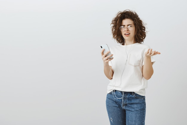 Frustrated and confused woman react to strange message on mobile phone, can't understand