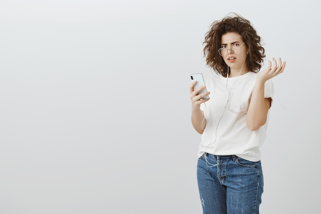 Frustrated and confused woman react to strange message on mobile phone