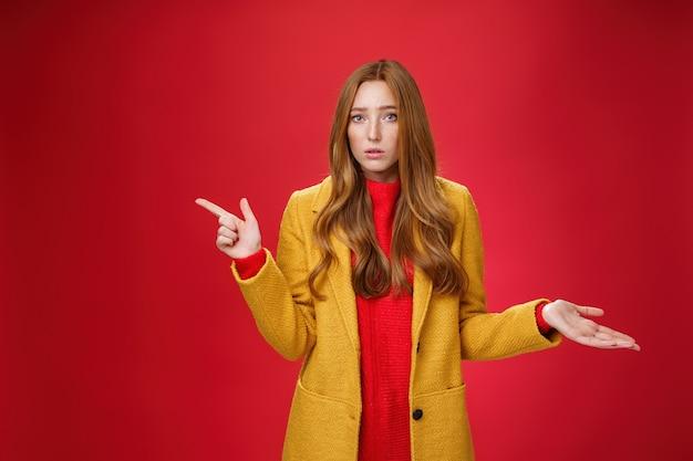 Giovane donna carina frustrata e confusa con i capelli rossi in cappotto giallo che si stringe nelle spalle mentre indicava la spiegazione in attesa di sinistra interrogata mentre poneva una domanda all'oscuro e perplessa su sfondo rosso.