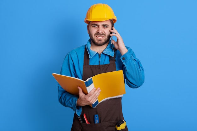 Frustrated construction foreman talking with employee on his cell phone, having angry facial expression, wearing blue uniform, yellow helmet and brown apron, posing isolated on color wall.