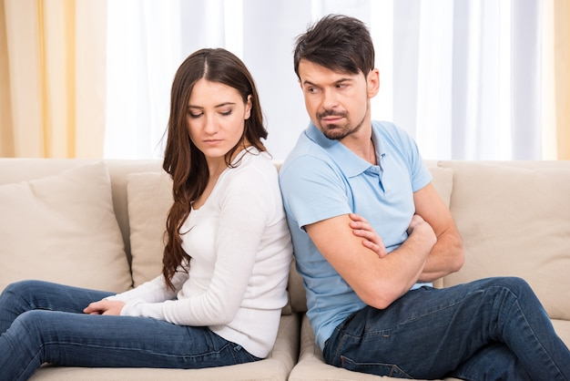 Frustrated couple are sitting on couch.