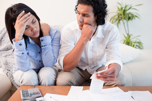 Frustrated couple checking their bills