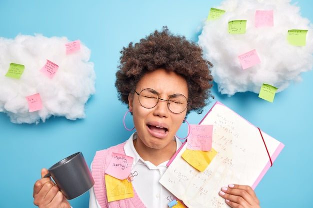 Frustrated crying schoolgirl holds folders and papers stuck with sticky notes drinks coffee feels tired of preparing coursework wears round spectacles poses against blue wall