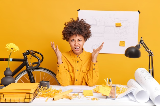Frustrated curly afro american female office worker raises palms looks angrily puzzled to make mistake poses at desktop in coworking space has mess on desktop