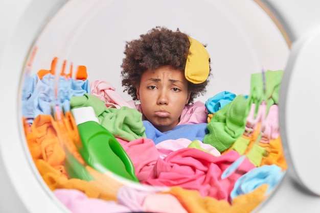 Frustrated curly afro american housewife feelstired after doing laundering poses inside of washing machine around dirty colorful clothes purses lower lip feels unhappy