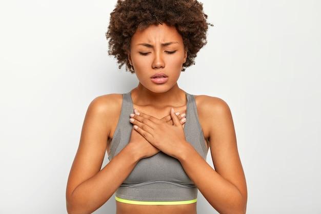 좌절 된 어두운 피부 아프리카 계 미국인 여자는 가슴에 급성 통증을 앓고 흰색 배경에 고립 된 회색 스포츠 브래지어를 착용합니다.