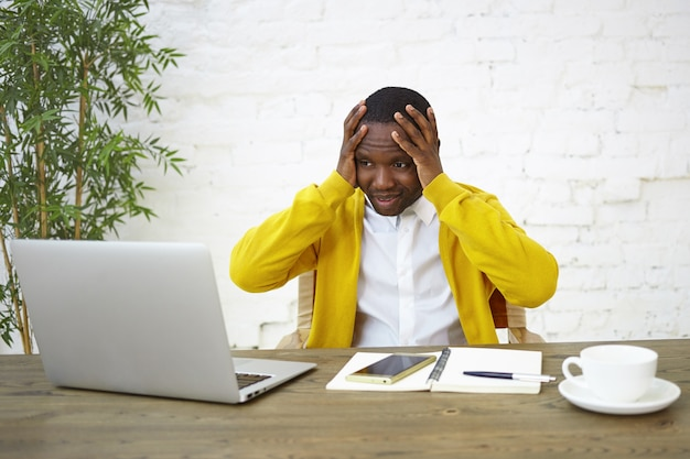 Frustrated dark skinned businessman sitting at workplace with hands on head, feeling stressed, looking at laptop screen in panic, unable to keep company afloat, having not enough money to run business