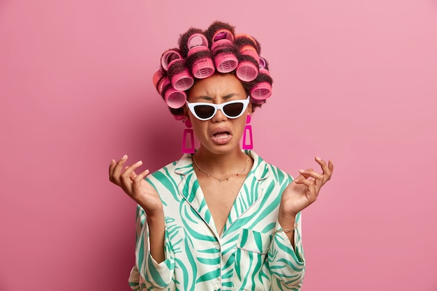 Frustrated dark skinned young woman being in bad mood, expresses negative emotions, raises hands with disappointment, feels bored and lonely, wears trendy sunglasses and hair curlers on head