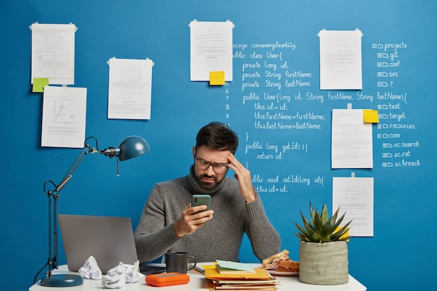 Frustrated depressed male freelancer cannot send message to client, looks sadly at smartphone, keeps hand on temple, suffers from headache