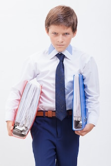 The frustrated and determined boy holding  folders in his hands over white background