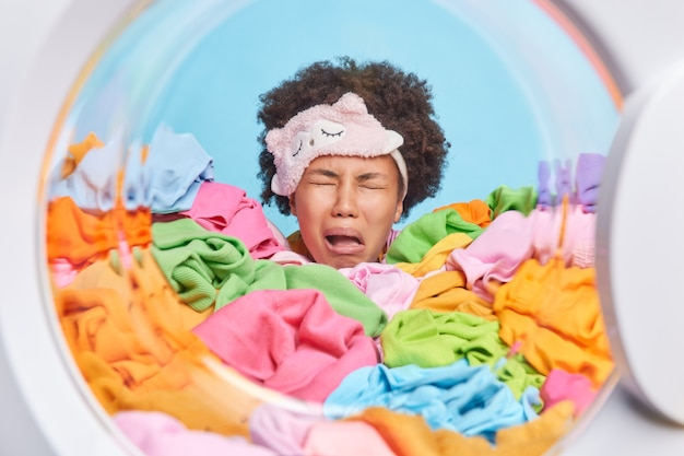 欲求不満の失望した縮れ毛の疲れた女性が疲れて泣く額に目隠しをして寝たいが洗濯物に囲まれた洗濯機のドラムで家事のポーズを終えなければならない
