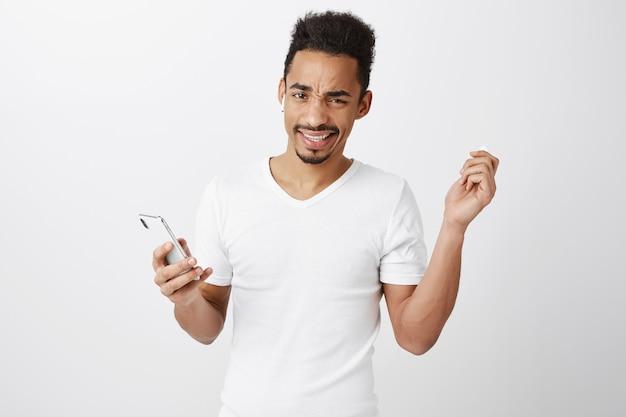 Frustrato e dispiaciuto auricolare da decollo ragazzo afro-americano e rabbrividire, tenendo il telefono cellulare
