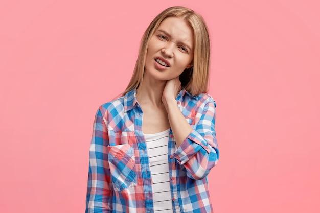 欲求不満の不機嫌な金髪の若いかわいい女性は首に強い痛みを持っています