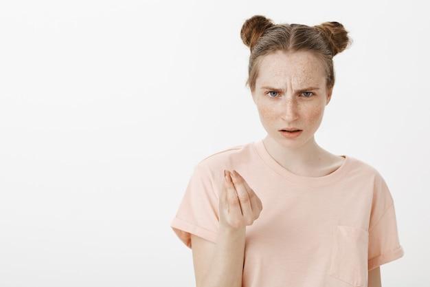 Adolescente frustrato e scontento in posa contro il muro bianco