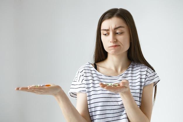 Frustrata dubbiosa giovane femmina caucasica accigliata e labbra increspate, non può scegliere quali antidolorifici prendere mentre si soffre di crampi