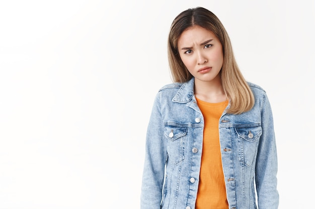 Frustrated doubtful young intense asian blond girl frowning cringe hesitant squinting suspicious have uncertain opinion cannot understand disliking hideous friend drunk behaviour, white wall