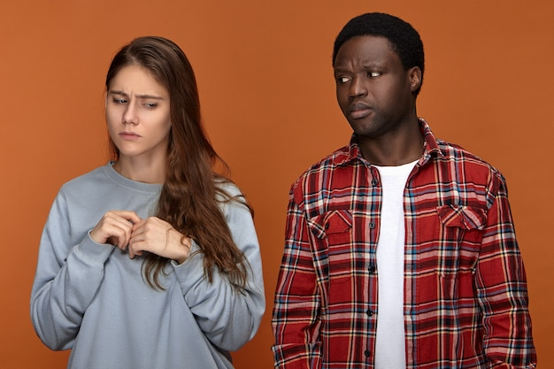 Frustrated european 20 year old girl feeling nervous because of disagreement with her dissapointed displeased african american boyfriend. people, ethnicity, relationships, quarrel and problems concept