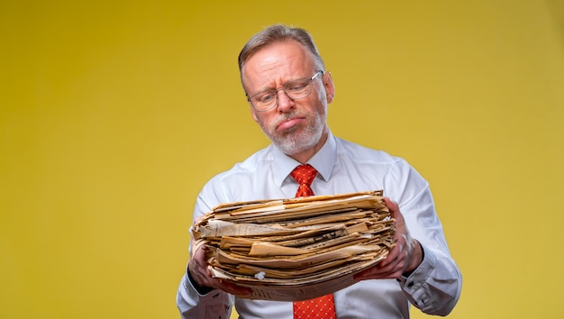 Frustrated executive worker over yellow background overworked holding piles of documents paper work.