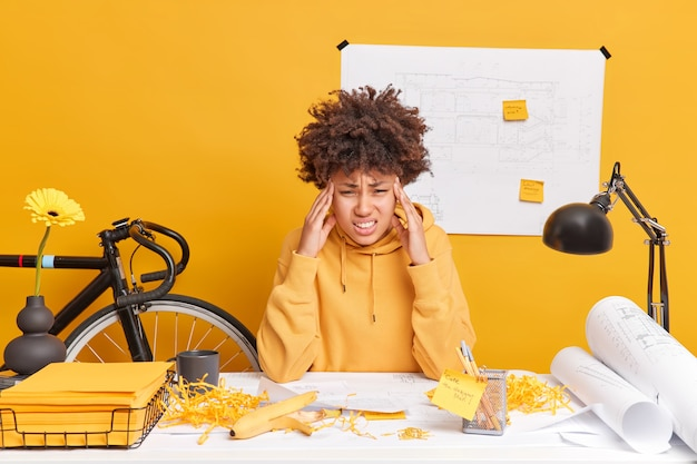 Frustrated exhausted afro american woman touches temples suffers from severe headache tired of working with papers prepares architectural project has difficult task