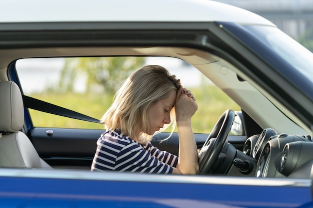 Frustrated female in car lying on steering wheel tired with closed eyes woman exhausted of problems