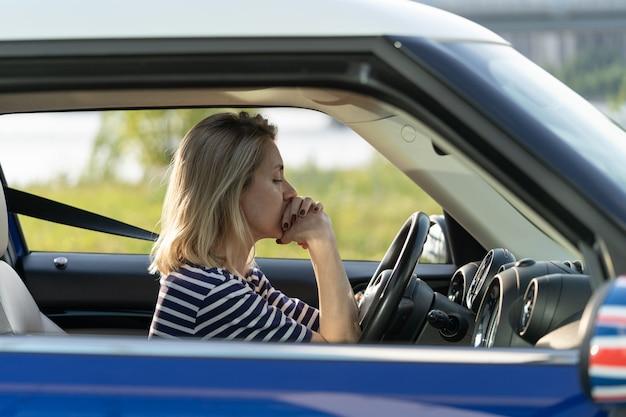 좌절한 여성 운전자는 차량 사고 후 운전하기 두려워 손에 턱을 대고 차 안에 앉아 있다