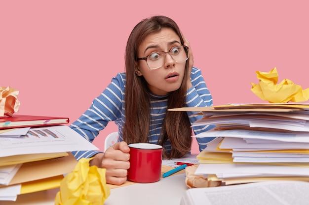 좌절 한 여성 고용주가 직장에서 포즈를 취하고, 표현을 두려워하고, 문서 작업을 두려워하고, 뜨거운 음료를 마신다.