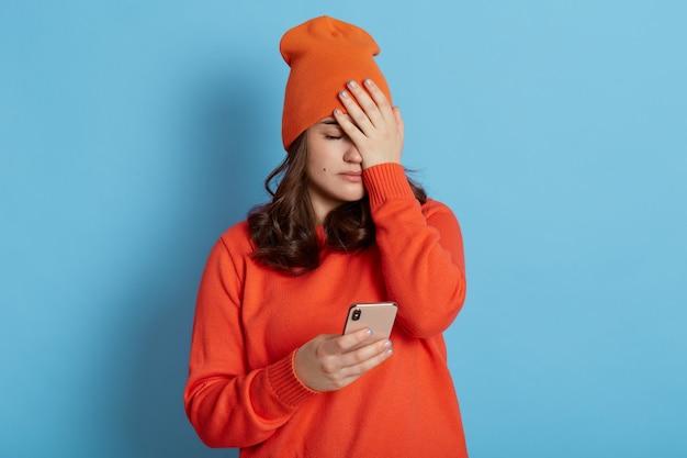 캐주얼 한 옷을 입고 좌절 한 여성, 손바닥으로 얼굴을 덮고, 손에 전화를 들고, 중요한 것을 잊어 버리고, 심한 실수를하고, 슬프고, 파란색 벽 위에 격리됩니다.