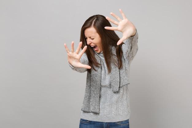 스웨터 스카프를 입은 좌절된 소녀는 손바닥이 회색 배경에 고립되어 외면하는 정지 제스처를 보여주며 소리를 질렀습니다. 건강한 패션 라이프 스타일 사람들의 감정, 추운 계절 개념. 복사 공간을 비웃습니다.