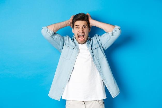 Ragazzo frustrato che perde, urla dispiaciuto e guarda la telecamera, tenendosi per mano sulla testa, in piedi su sfondo blu