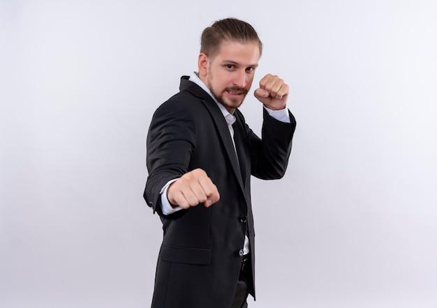 白い背景の上に立っているボクサーのようにポーズをとって拳を握り締めるスーツを着て欲求不満のハンサムなビジネスマン