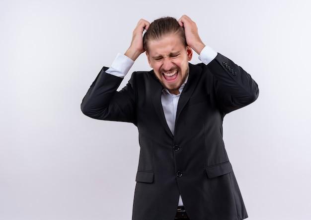 Uomo d'affari bello frustrato che indossa la tuta che si scatena tirando i capelli in piedi su sfondo bianco
