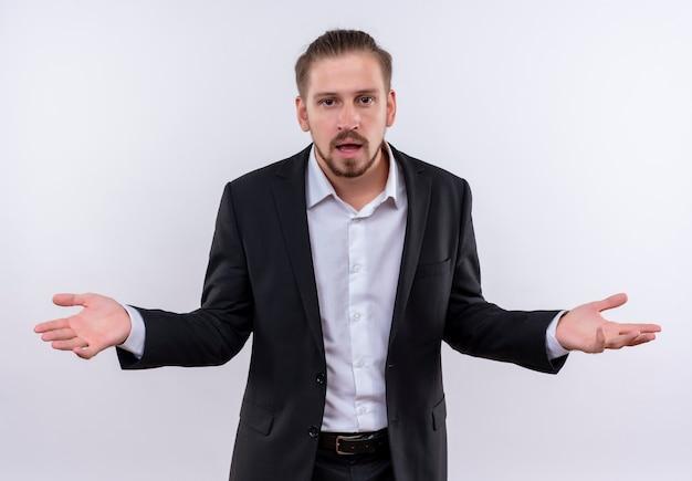 白い背景の上に立って混乱しているカメラを見てスーツを着て欲求不満のハンサムなビジネス男