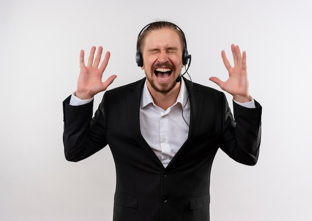 Frustrated handsome businessman in suit and headphones with a microphone shouting and yelling with aggressive expression standing over white background