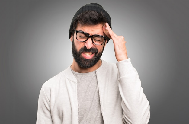 Frustrated hipster man on grey background
