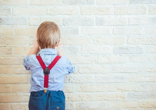 壁の近くに立っている欲求不満の小さな男の子が背を向けた