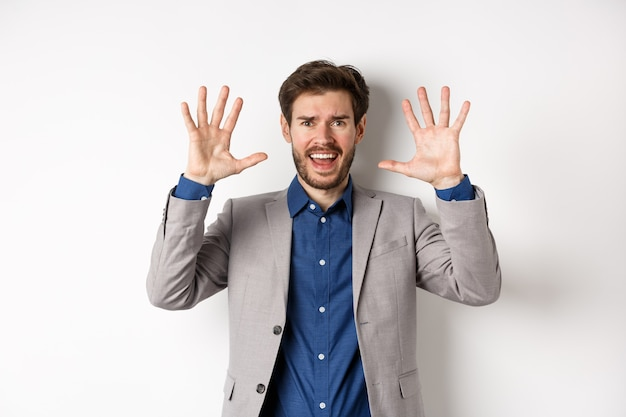 Разочарованный человек сдаётся, поднимает руки в знак капитуляции и кричит, спорит, одет в костюм и выглядит обеспокоенным, белый фон.