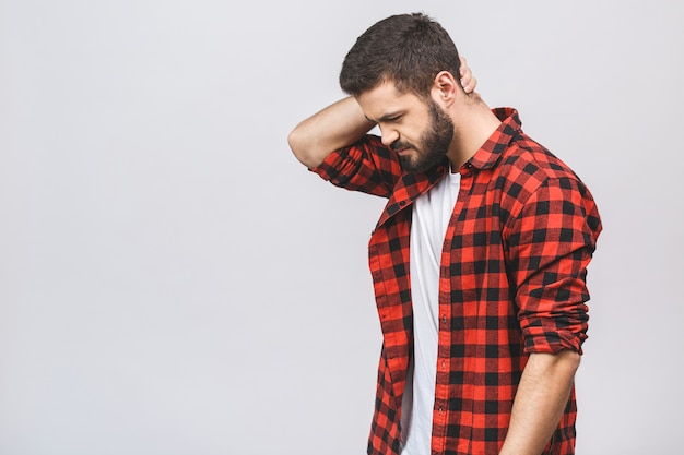 Frustrated man holding hand on his neck, having pain on the back. hipster male with beard in red plaid checkered shirt isolated on white studio background.