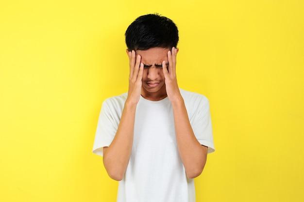 그의 머리를 잡고 좌절된 남자입니다. 노란 배경에 고립되어 머리를 잡고 있는 좌절한 남자의 몸짓을 하는 젊은 아시아 남자