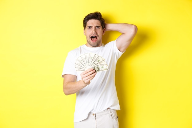 Frustrated man holding money, shouting and panicking, standing over yellow background.