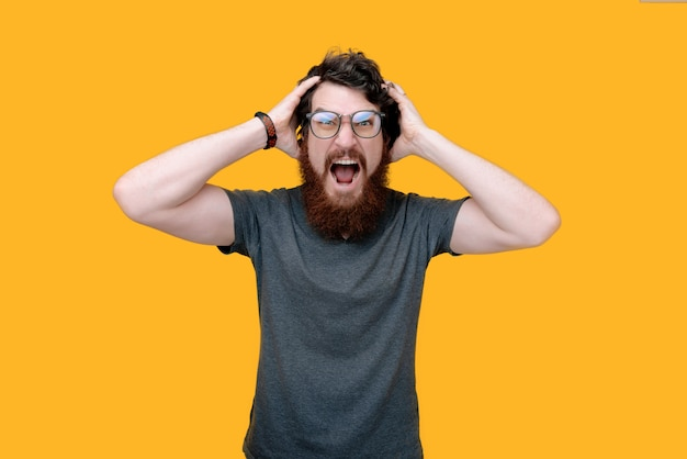 Frustrated man, putting hands on head and scraming on yellow