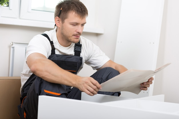 Разочарованный мужчина читает инструкцию и собирает мебель самостоятельно. сделай сам, новый дом и концепция переезда
